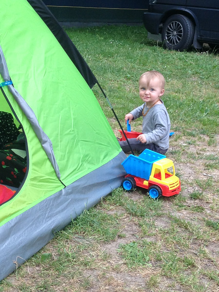 Child playing next to green tent.