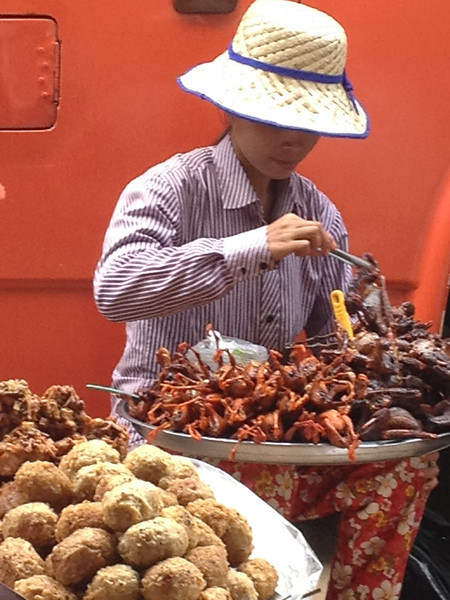 Vendor with a large tray of fried birds.